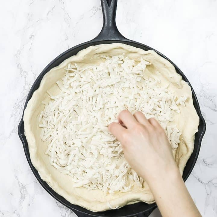 Hand sprinkling cheese on pizza dough in cast iron pan