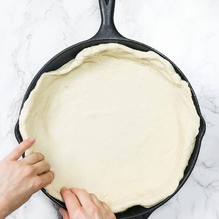 Hands pressing pizza dough into cast iron pan