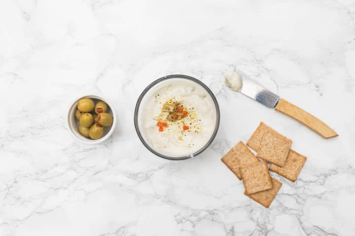 Small bowl of cheese with olives and crackers
