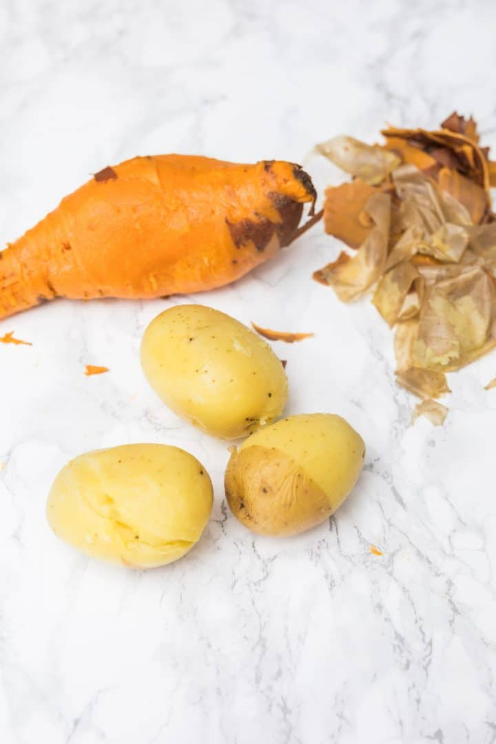 Peeled sweet potato and Yukon gold potatoes on counter with peels to the side