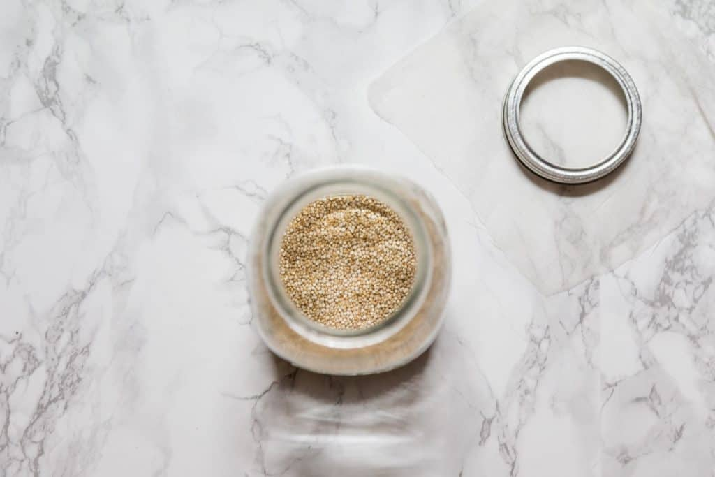 Overhead photo of dry quinoa in glass jar