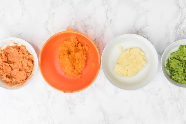 Four bowls of colorful mashed potatoes