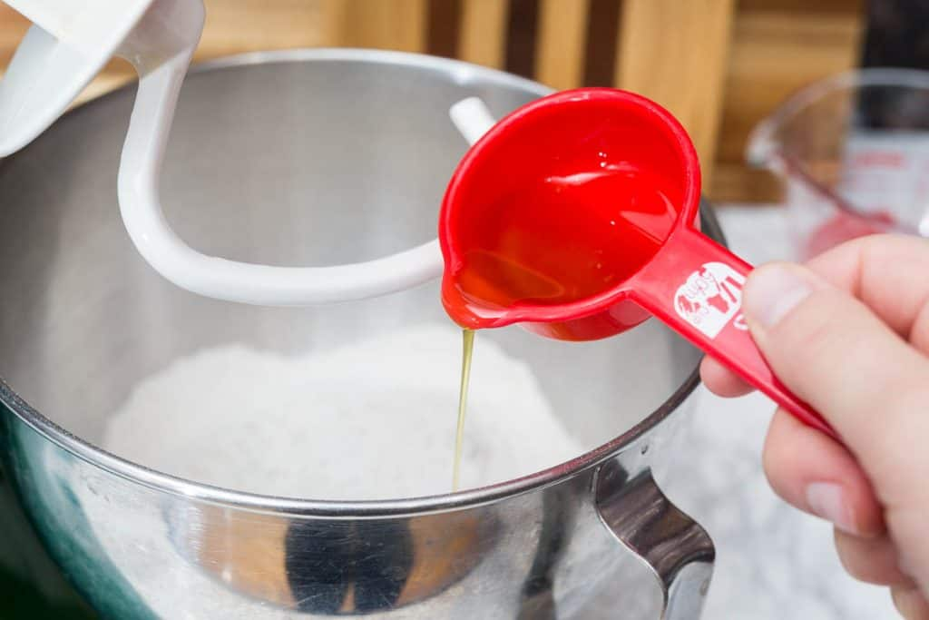 Hand pouring olive oil from measuring cup into stand mixer