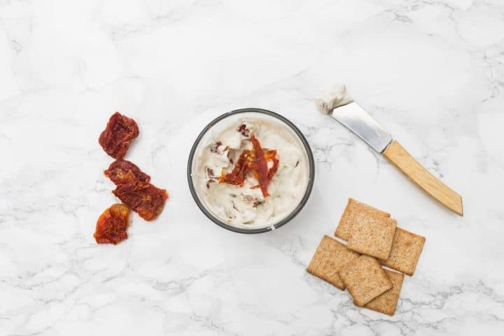 Small bowl of cheese with sundried tomatoes and crackers