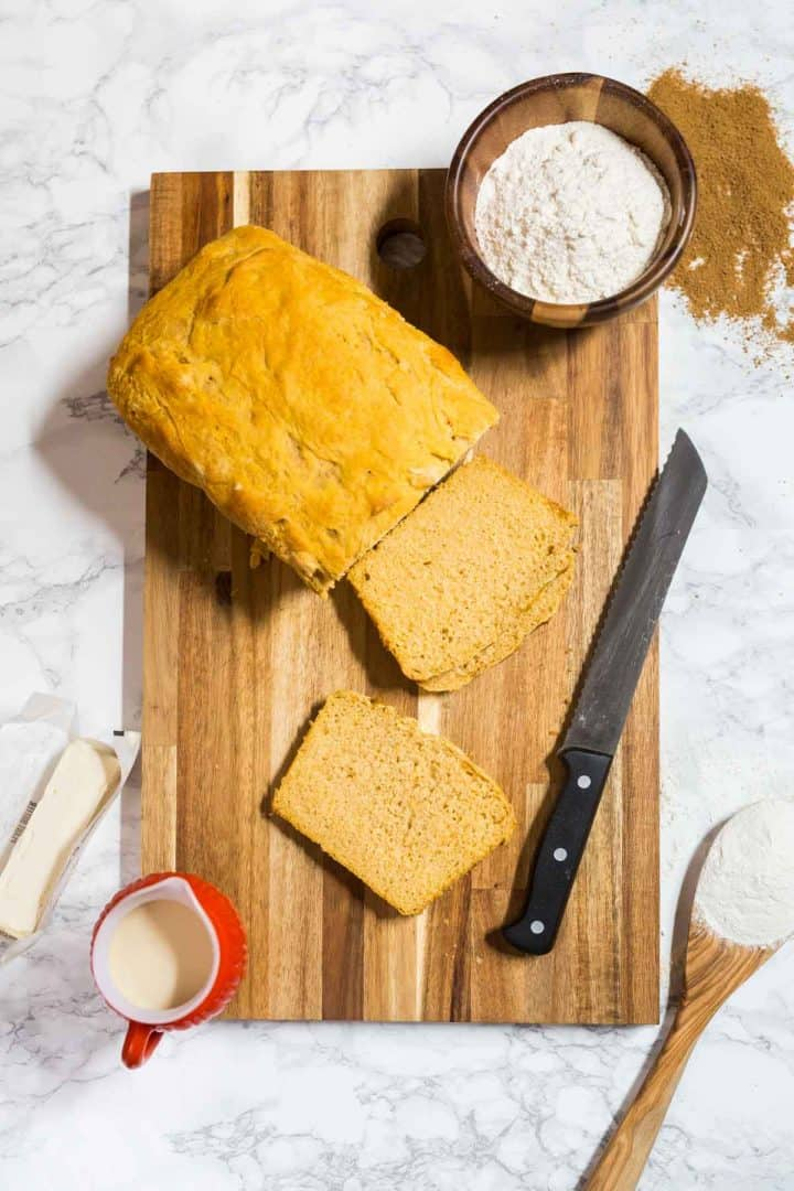Loaf of sweet potato bread with slices cut out surrounded by ingredients