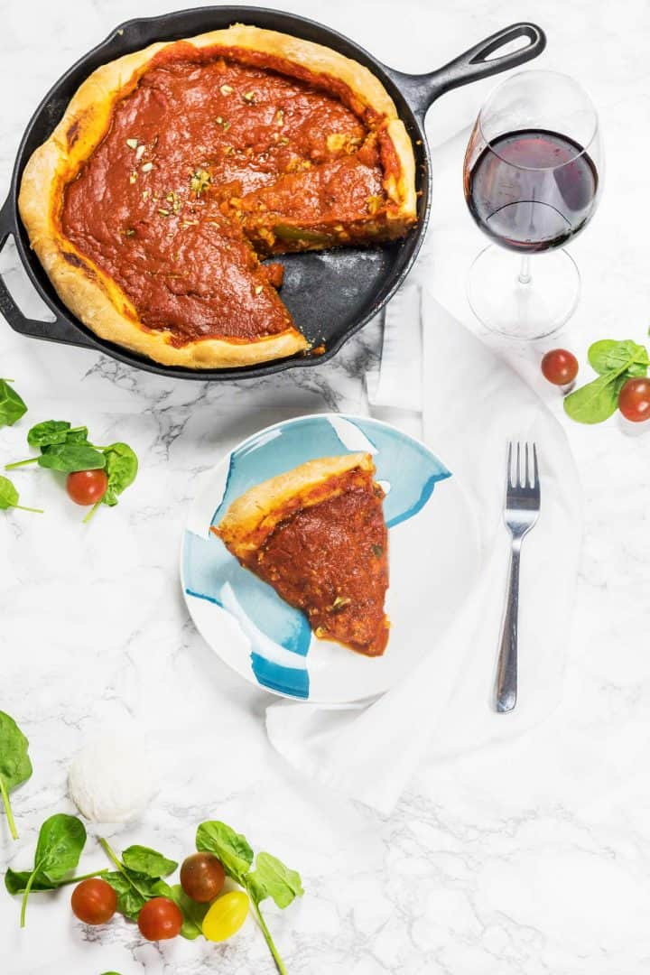 Deep dish pizza baked in a cast iron pan with slice cut out on plate with glass of red wine
