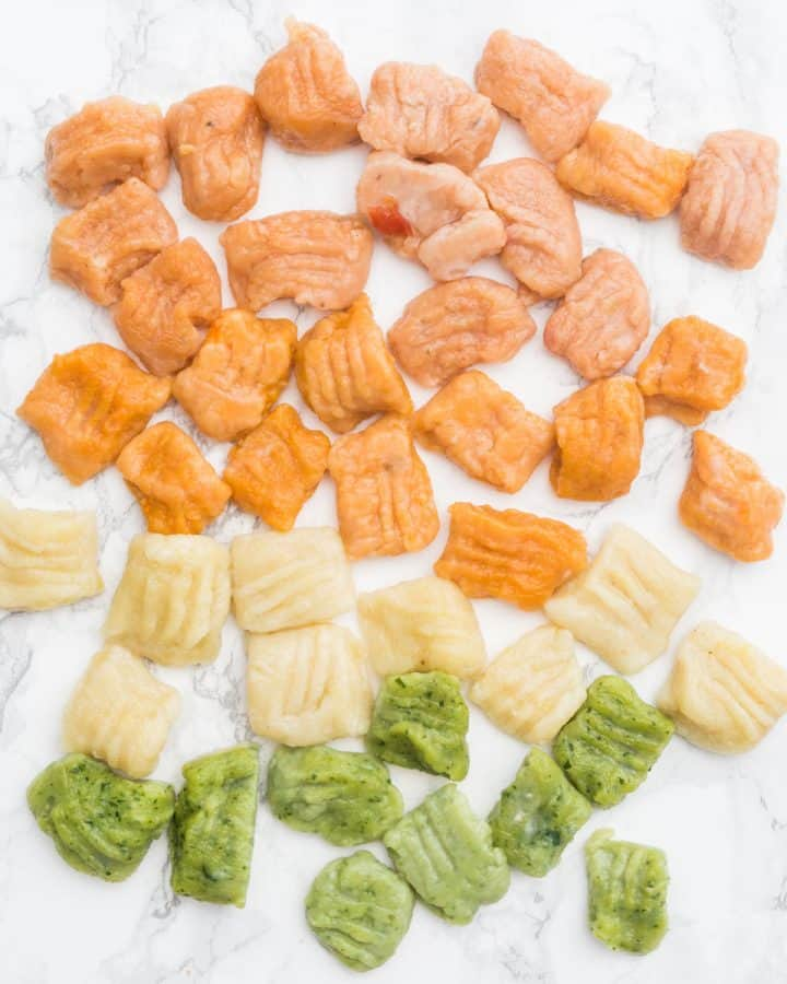 Red, orange, plain, and green gnocchi on marble counter