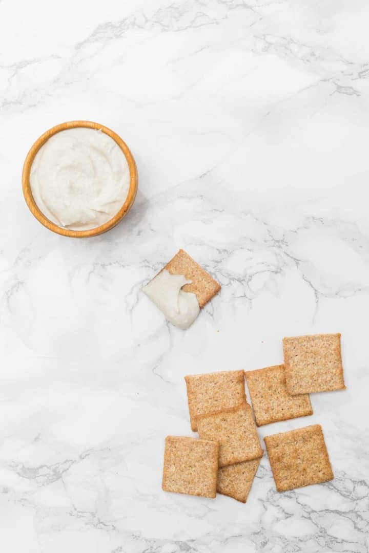 Small bowl of spreadable cheese and crackers on marble counter