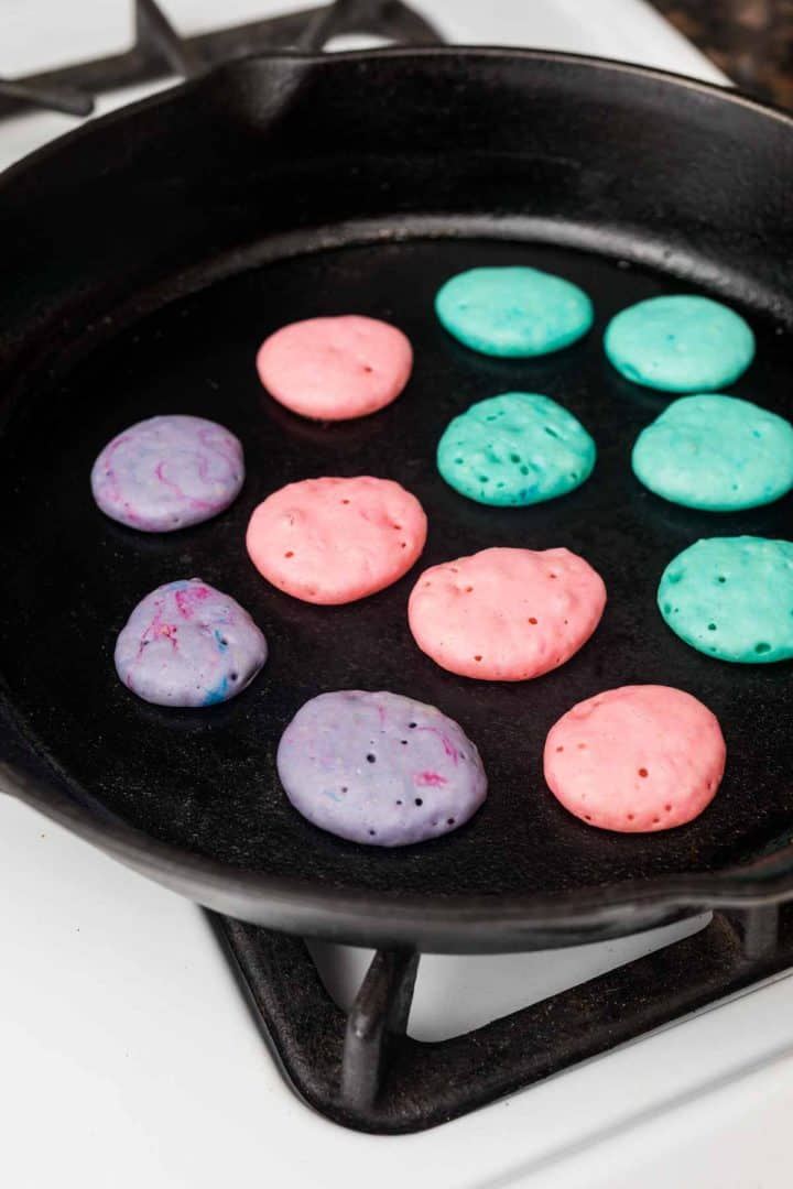 Tiny colorful pancakes in pan on stove