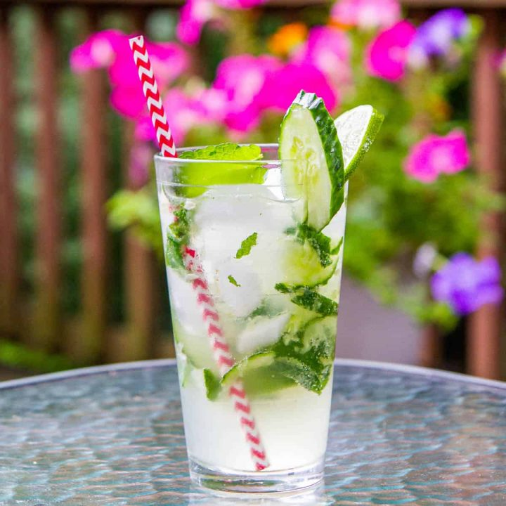 Cucumber mojito with mint, limes, and cucumbers in a pint glass with a red straw