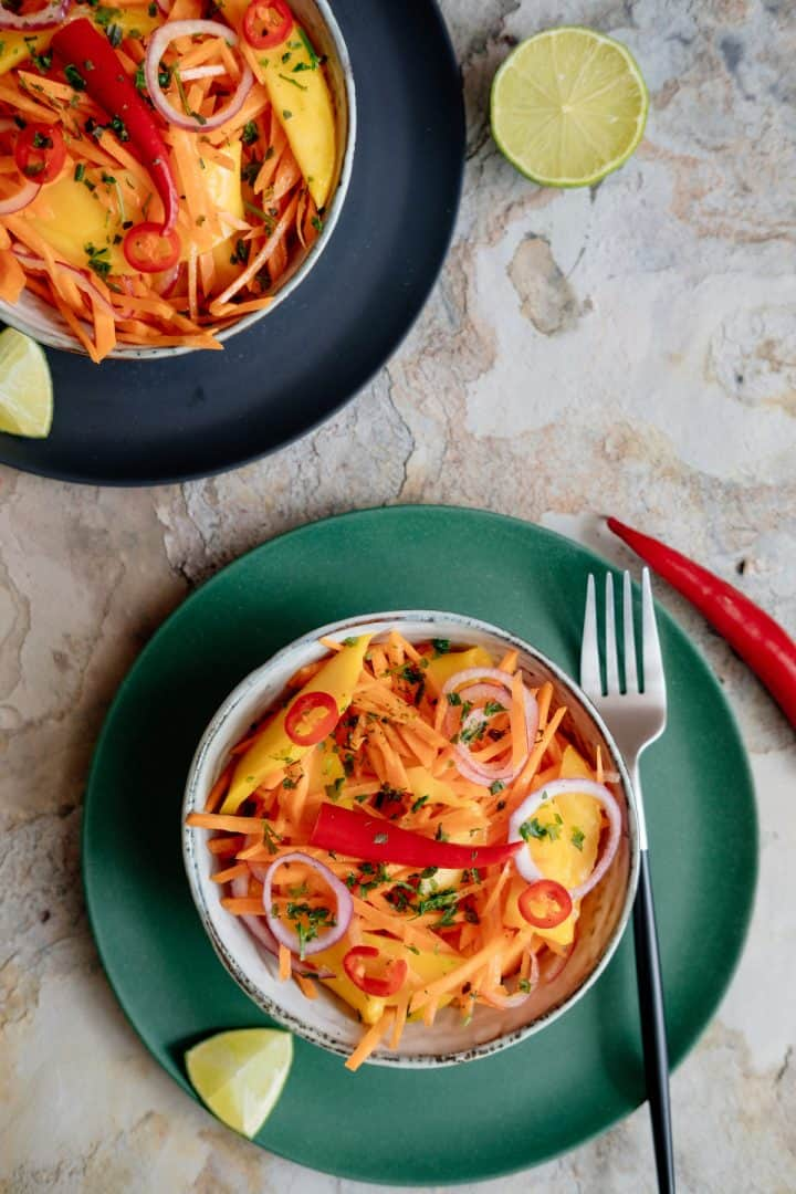 Overhead photo of two bowls of raw carrot mango salad with red chilis