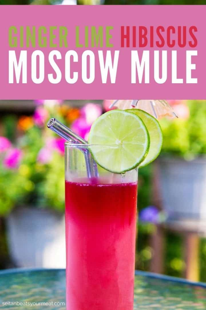 "Pink cocktail with lime slices with text ""Ginger Lime Hibiscus Moscow Mule"""