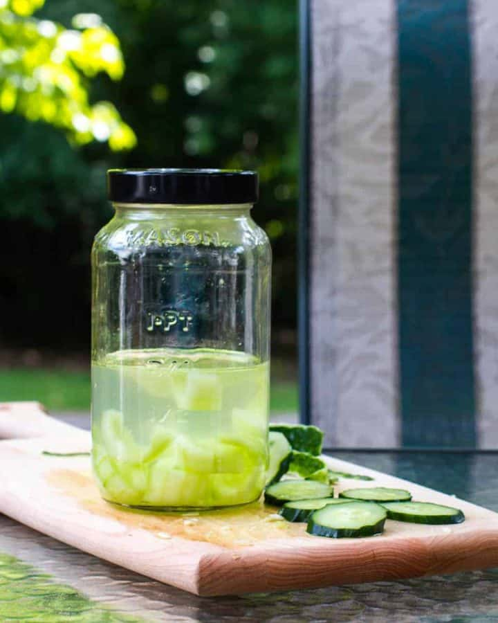 Jar of cucumber vodka on cutting board outdoors with cucumber slices