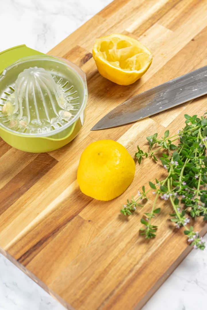 Two lemon halves, a knife, a lemon juicer, and a bundle of thyme on a cutting board