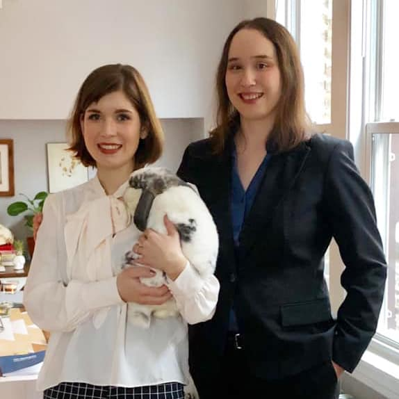 Two women in photo with one holding a gray and white rabbit