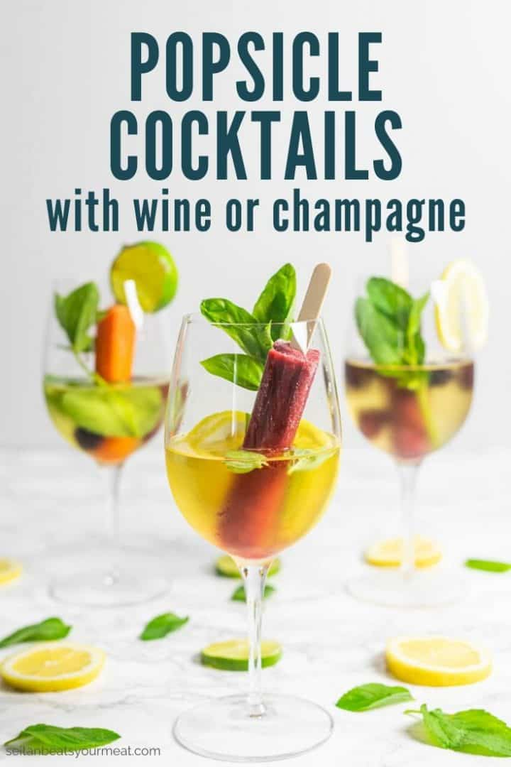 """Three glasses of wine with a popsicle, lemon and lime slices, and fresh herbs with text """"Popsicle Cocktails with wine or champagne"""""""