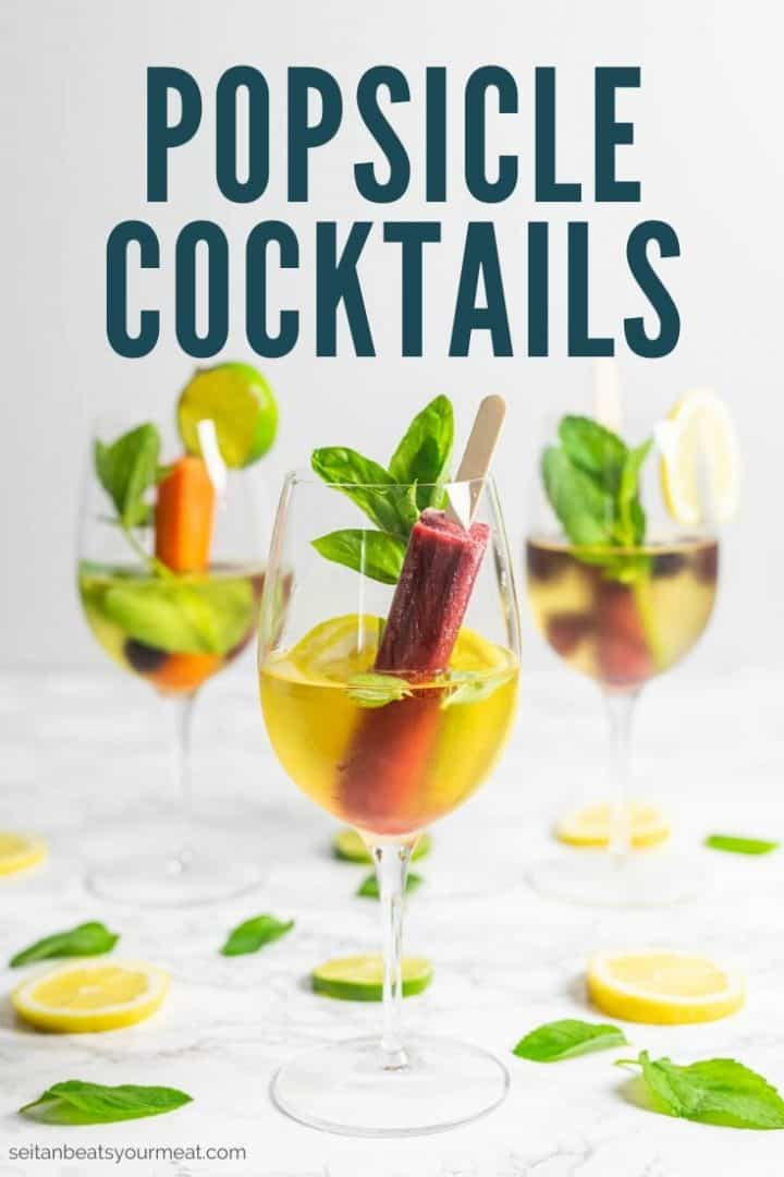 """Three glasses of wine with a popsicle, lemon and lime slices, and fresh herbs with text """"Popsicle cocktails"""""""