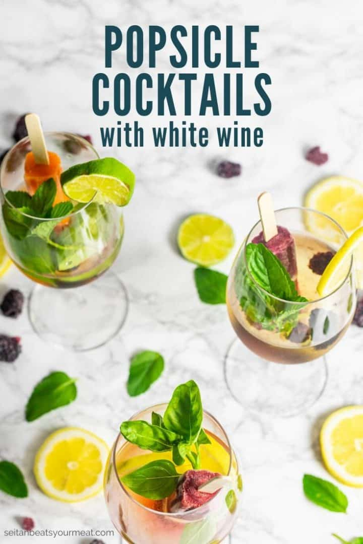"""Three glasses of wine with a popsicle, lemon and lime slices, and fresh herbs with text """"Popsicle Cocktails with White Wine"""""""