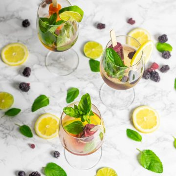 Three glasses of wine with a popsicle, lemon and lime slices, and fresh herbs
