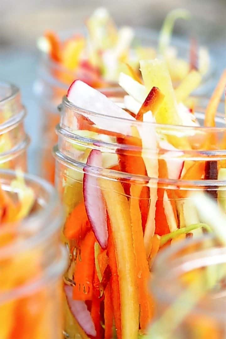 Julienned rainbow carrots and radishes in a mason jar