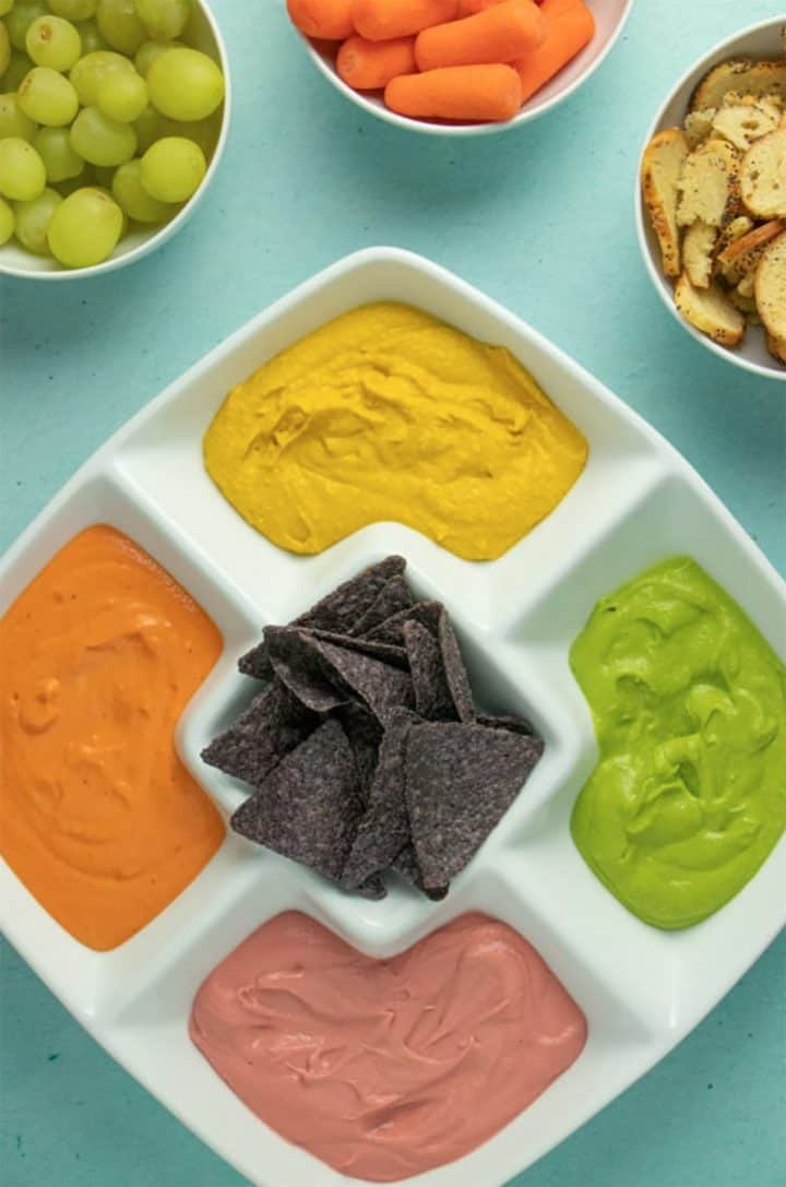 Pink, orange, yellow, and green hummus in a platter with blue tortilla chips