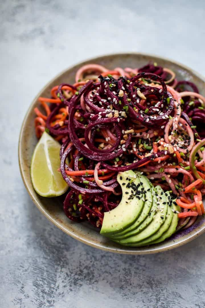 Bowl of spiralized vegetables with sesame seeds, avocado, and dressing