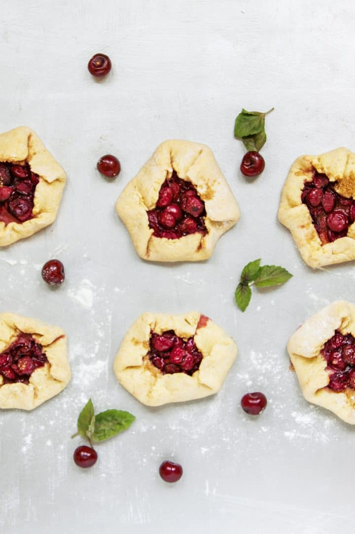 Six cherry galettes on gray background sprinkled with flour with mint leaves and cherries