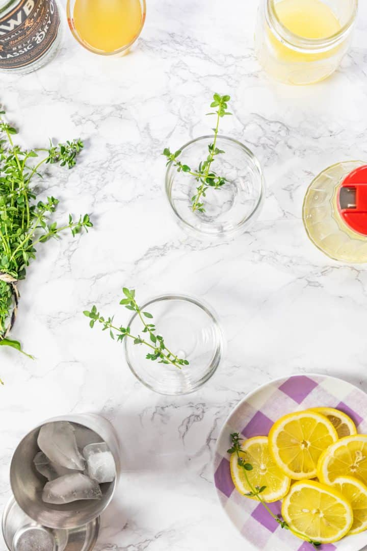 Two empty whiskey glasses with thyme sprigs surrounded by cocktail ingredients