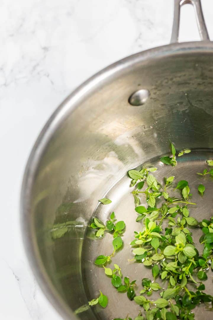 Close up of saucepan with cooked simple syrup and thyme leaves