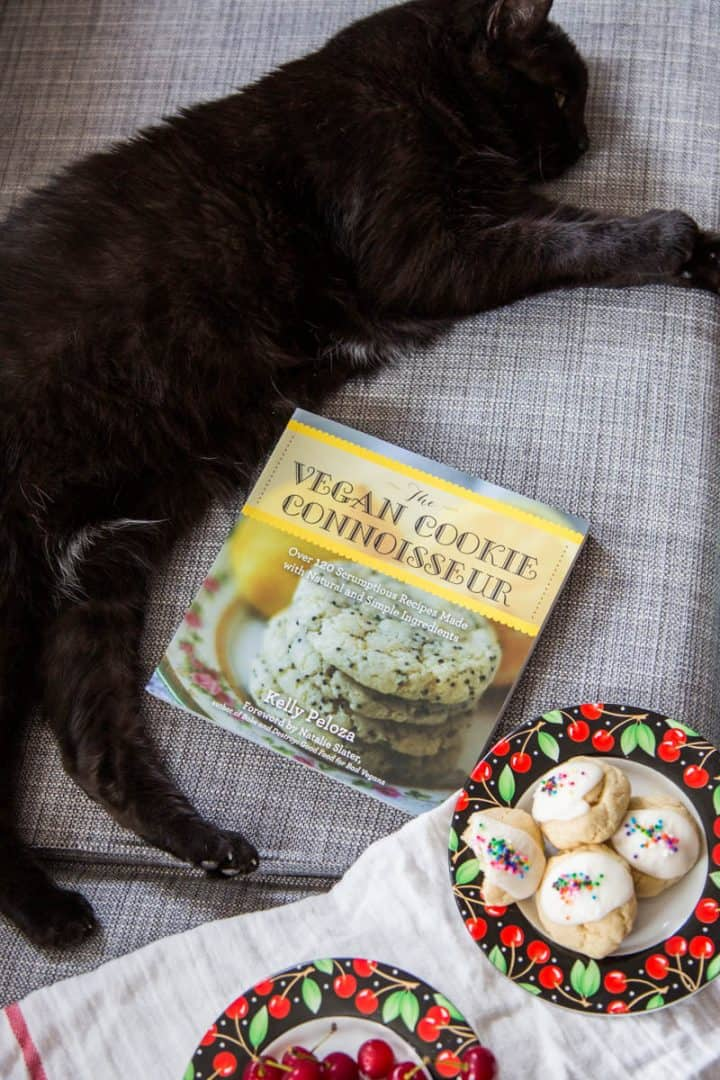 The Vegan Cookie Connoisseur cookbook on gray couch with black cat and plate of cookies