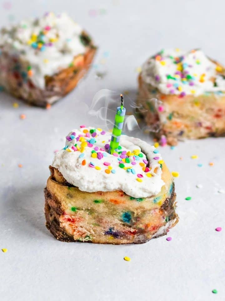 Cinnamon roll with frosting and colorful sprinkles and a recently blown out candle on top