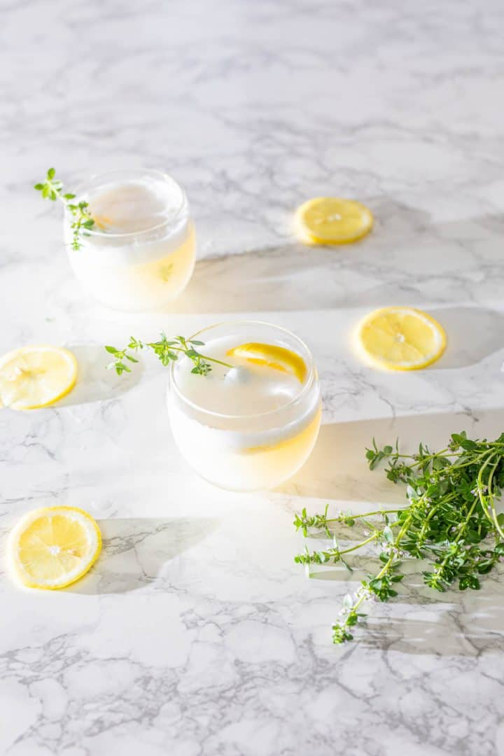 Two gin cocktails with lemon slices and fresh thyme