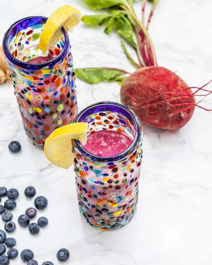 Two magenta smoothies with lemon slices with fresh beet and blueberries