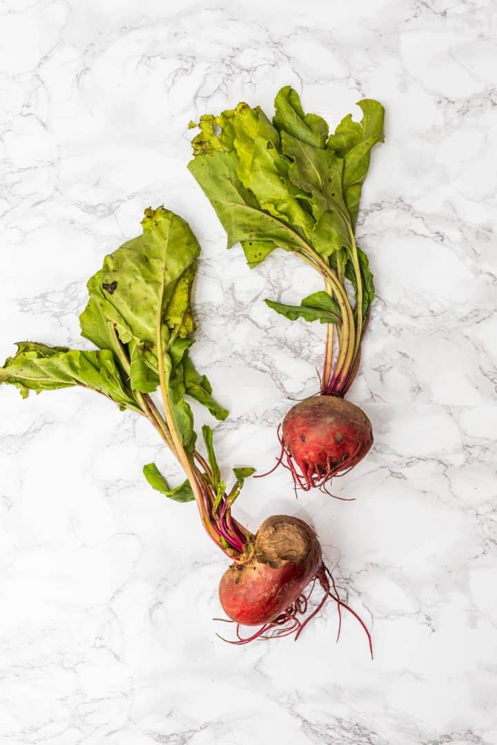 Two beets with greens attached on white marble surface