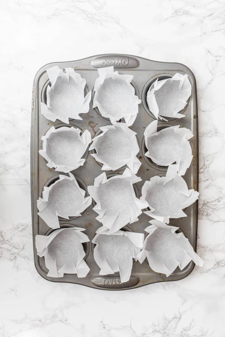 Muffin tray filled with parchment paper liners
