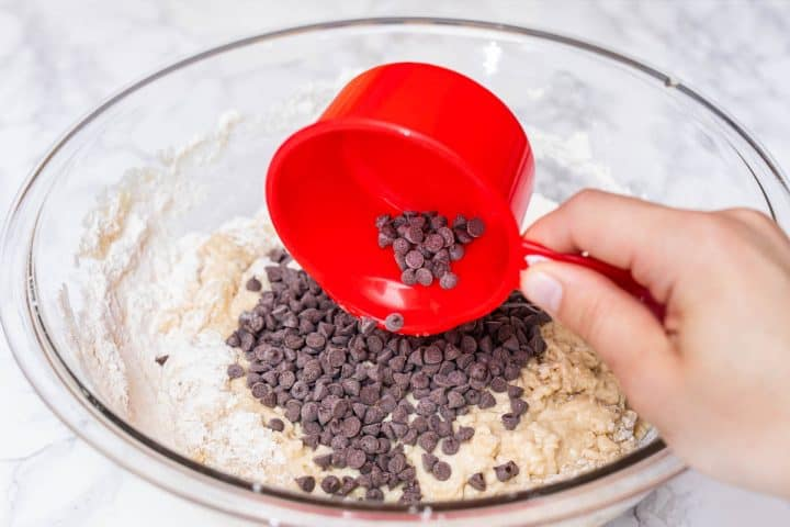 Hand pouring mini chocolate chips in muffin batter