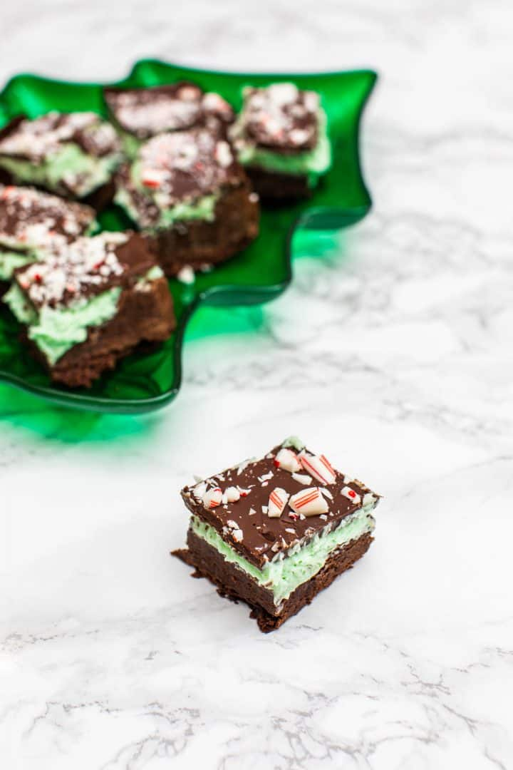 Chocolate peppermint cream bar with green tray of bars in the background