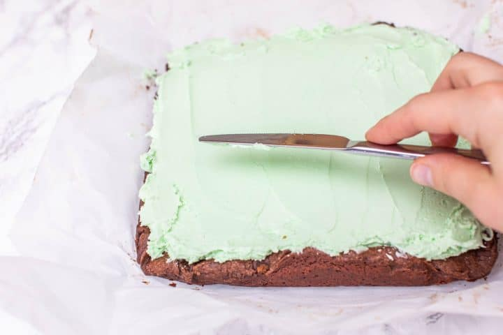 Spreading green frosting on tray of brownies