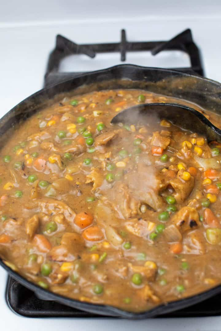 Thick gravy and vegetables in cast iron pan