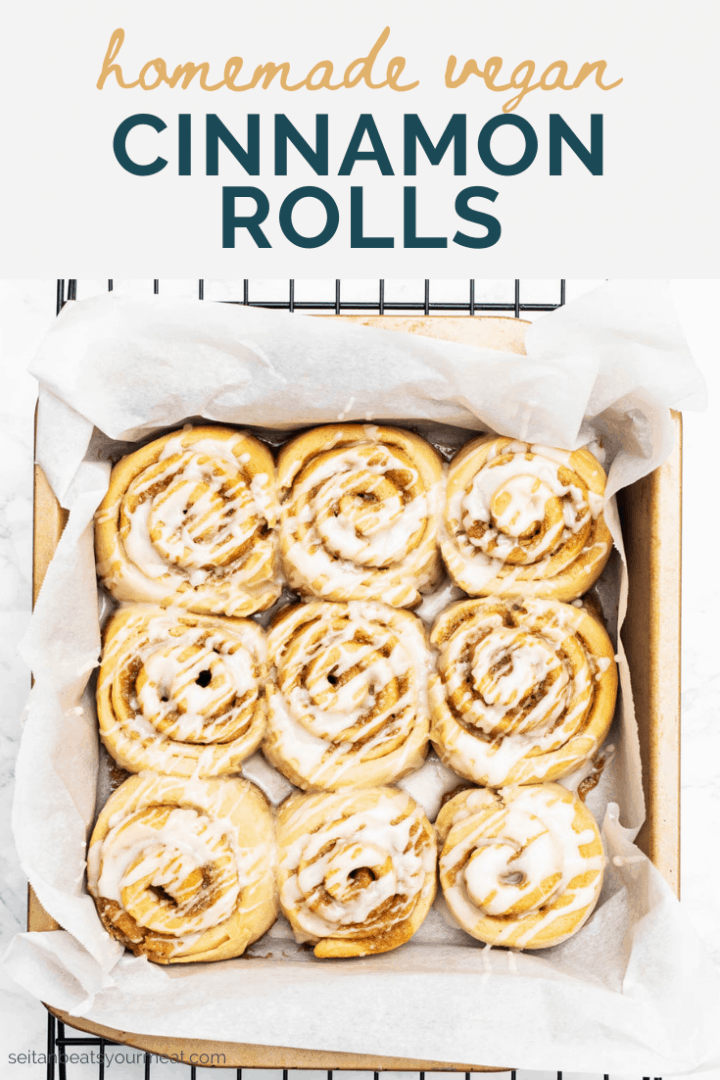 "Tray of glazed cinnamon rolls on cooling rack with text ""homemade vegan cinnamon rolls"""