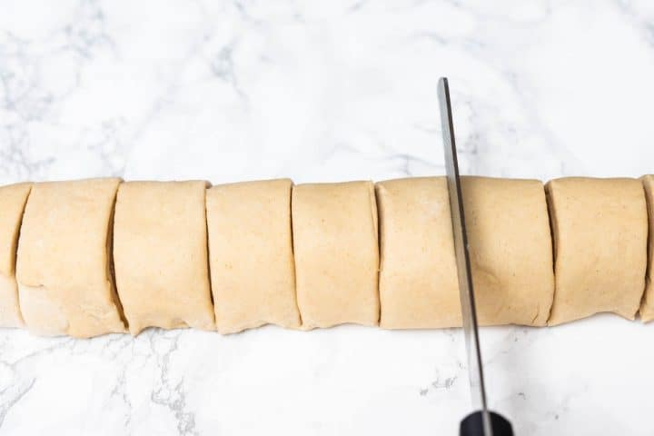 Knife cutting log of cinnamon roll dough into even slices
