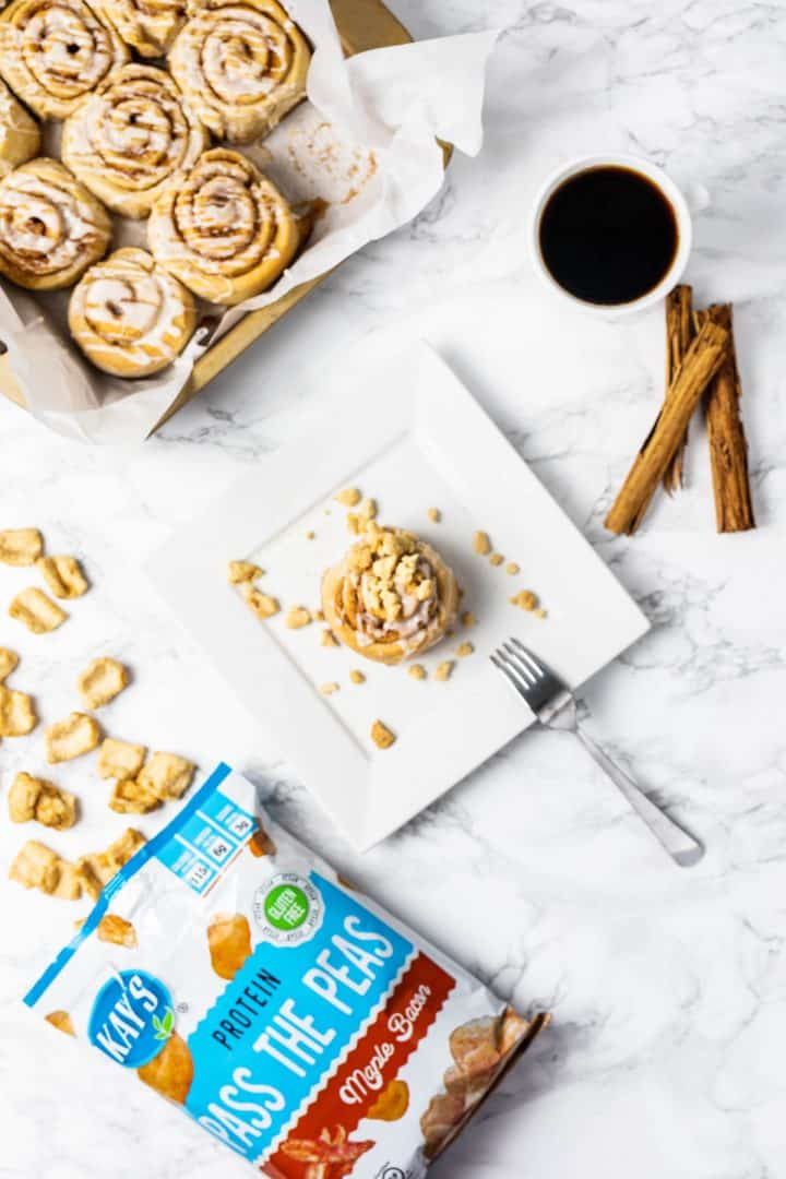 Cinnamon roll on plate with fork and cup of coffee, tray, and bag of snacks off to side