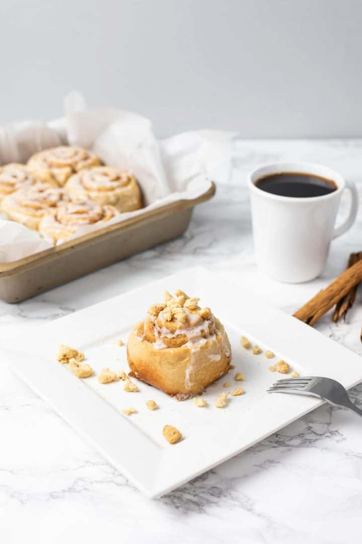 Cinnamon roll on plate with cup of coffee and tray of cinnamon rolls in background
