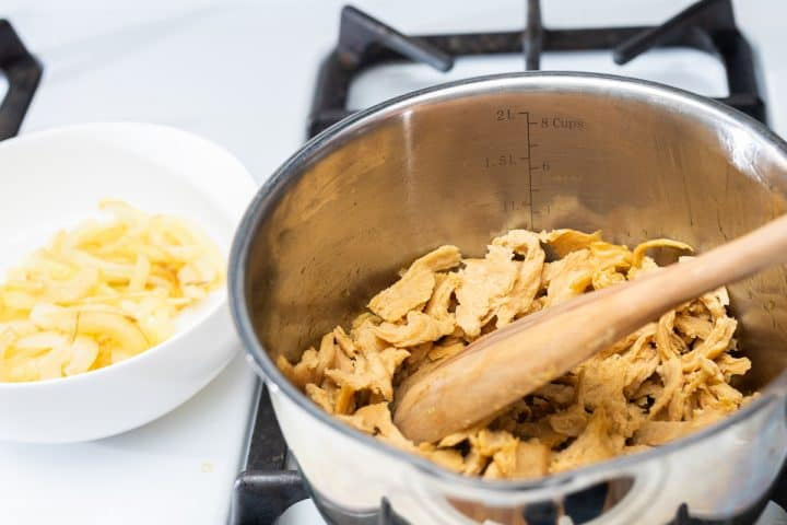 Shredded seitan in pot on stove with bowl of caramelized onions on side