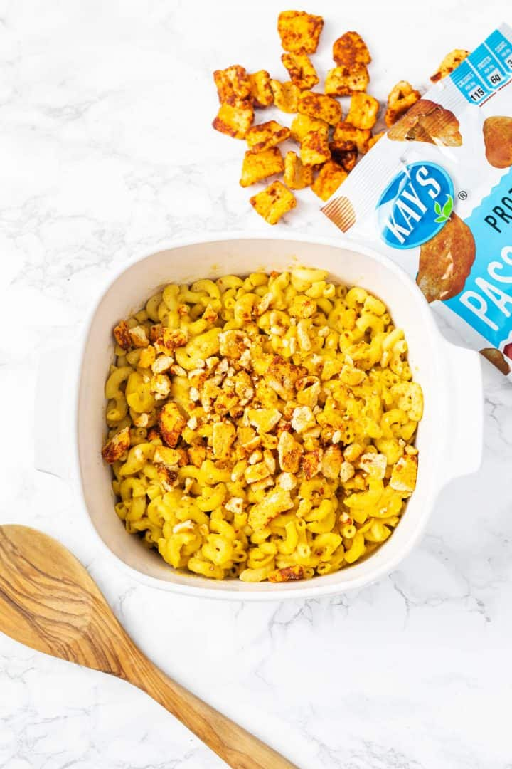 Baking dish filled with mac n cheese topped with bbq chips with bag of chips on side