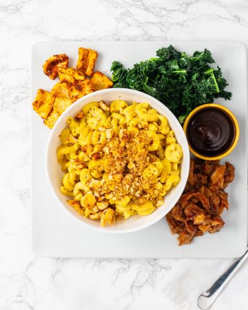 Bowl of vegan mac n cheese in plate with kale, seitan, and barbecue sauce