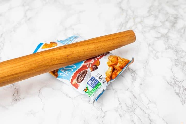 Rolling pin smashing bag of chips