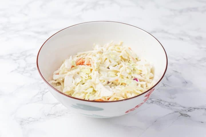 Bowl of vegan coleslaw on marble counter