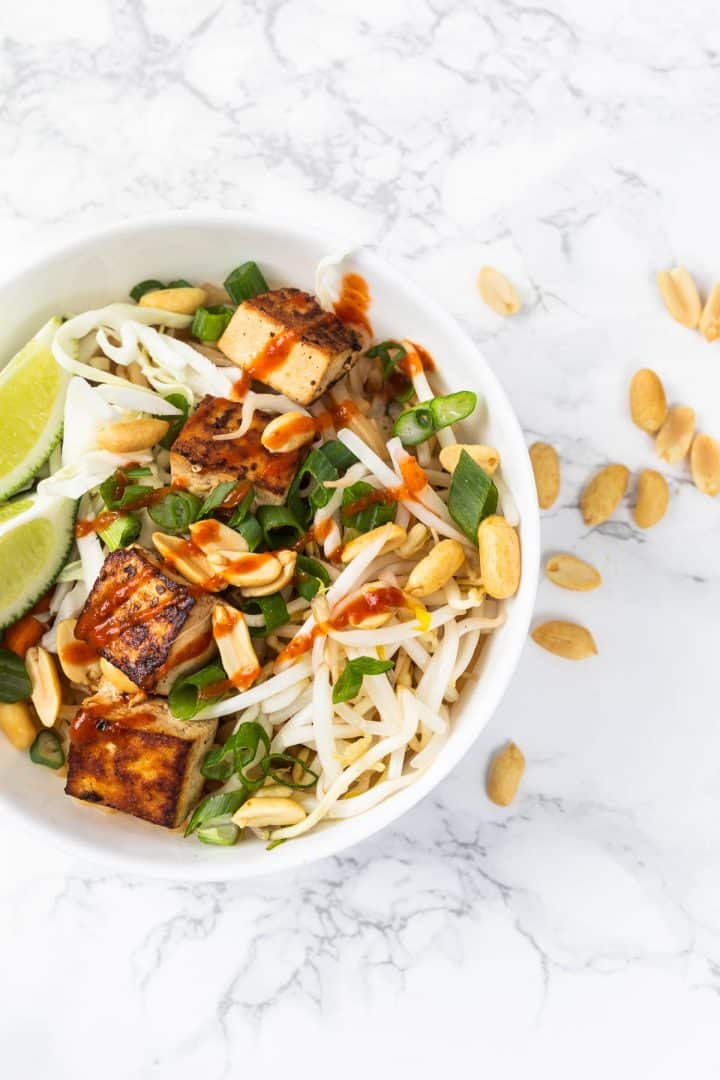 Bowl of tofu pad thai with peanuts on marble counter