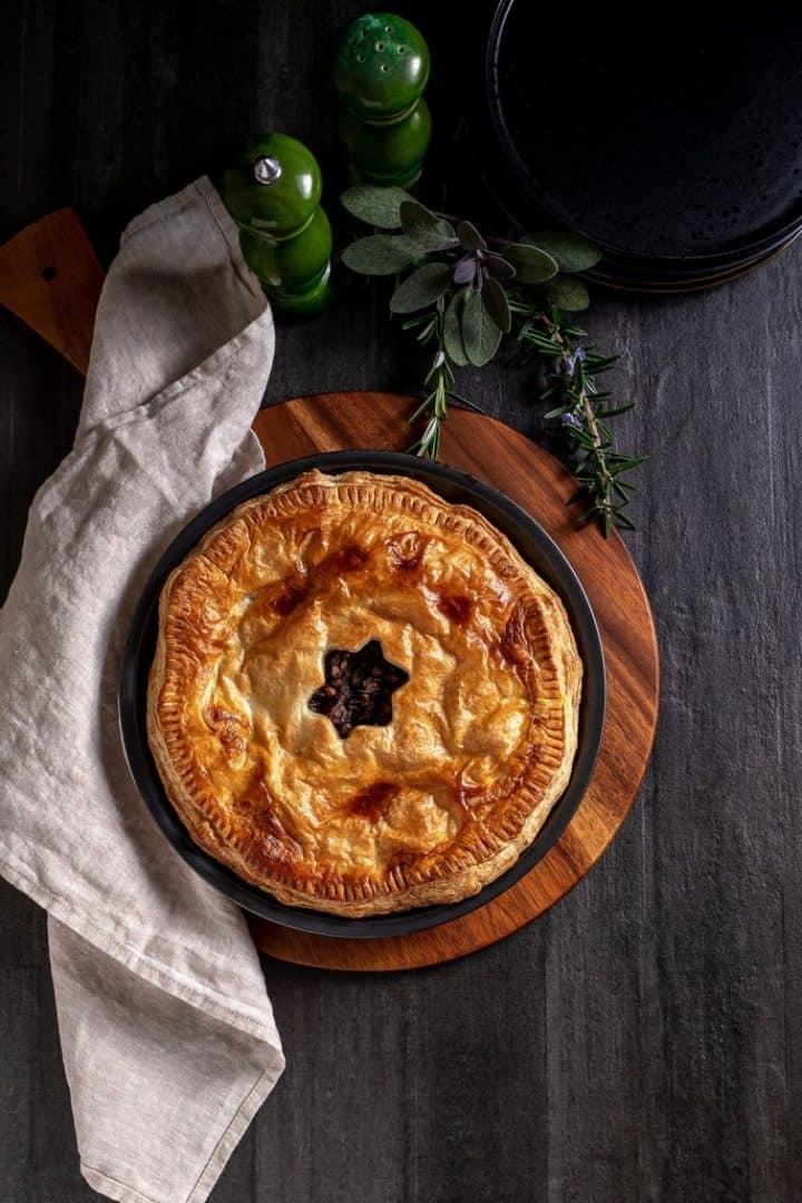 Savory mushroom pie on dark counter with dish towel